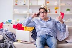 L'étude travaillante de jeune homme dans la chambre malpropre Photo stock