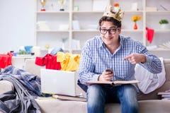 L'étude travaillante de jeune homme dans la chambre malpropre Image stock
