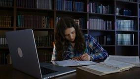 L'étudiant écrit dans un carnet dans la bibliothèque 4K banque de vidéos
