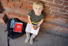 L'étudiant avec le grand sac à dos s'est assis pour manger son déjeuner près du bâtiment scolaire Repas scolaires images stock