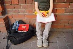 L'étudiant avec le grand sac de sac à dos et de déjeuner s'est assis pour manger son déjeuner près du bâtiment scolaire Repas sco images libres de droits