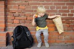 L'étudiant avec le grand sac de sac à dos et de lanch s'est assis pour manger son lanch près du bâtiment scolaire Repas scolaires photographie stock