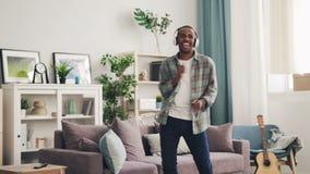 L'étudiant bel d'Afro-américain danse à la maison ayant l'amusement écoutant la musique avec des écouteurs belle lumière banque de vidéos