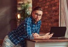 L'étudiant bel tient un smartphone tout en se penchant sur une table dans une chambre avec un intérieur de grenier Images libres de droits
