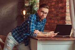 L'étudiant bel tient un smartphone tout en se penchant sur une table dans une chambre avec un intérieur de grenier Photo stock