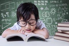L'étudiant d'école primaire lit des manuels dans la classe Image stock