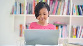 L'étudiant d'école primaire utilise l'ordinateur portable dans la bibliothèque clips vidéos