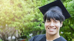 L'étudiant d'homme sourit et sentir heureux dans les robes et le chapeau d'obtention du diplôme images stock