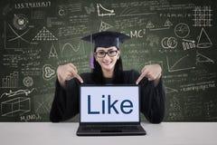 L'étudiant d'obtention du diplôme montrant comme sur l'ordinateur portable a tiré dans la classe Images stock