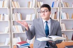 L'étudiant de droit des affaires avec la loupe lisant un livre images libres de droits