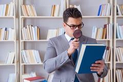 L'étudiant de droit des affaires avec la loupe lisant un livre photographie stock
