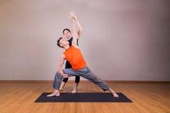 L'étudiant de guidage d'instructeur de yoga exécutent la pose prolongée d'angle latéral photographie stock libre de droits