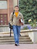 L'étudiant de marche avec des livres dans des mains photo stock