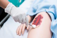L'étudiant de soins ont été formés comment blesser le patient de soin Elle pratiquent s'exercer avec la poupée du patient, avant  Images stock