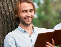 L'étudiant de sourire en parc de campus a lu un livre Photos libres de droits