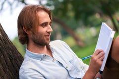 L'étudiant de sourire en parc de campus a lu un livre Images libres de droits