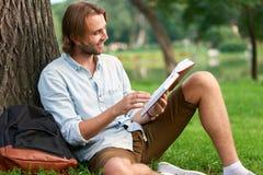 L'étudiant de sourire en parc de campus a lu un livre Image libre de droits