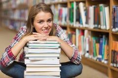 L'étudiant de sourire s'asseyant sur la bibliothèque parquettent le penchement sur la pile des livres Photographie stock libre de droits
