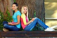 L'étudiant deux féminin de sourire s'asseyent sur le banc Image stock
