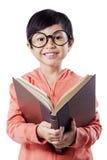L'étudiant doux d'école primaire lit des livres Images stock