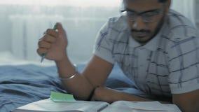 L'étudiant en gros plan et indien en verres enseigne des leçons, se trouvant sur un lit dans une salle de dortoir banque de vidéos