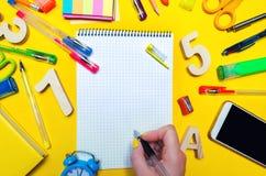 L'étudiant fait des notes dans un carnet Copiez l'espace Instruisez les accessoires sur un bureau sur un fond jaune Concept d'édu Images libres de droits