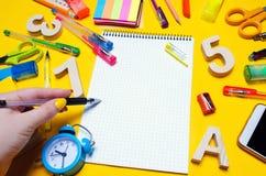 L'étudiant fait des notes dans un carnet Copiez l'espace Instruisez les accessoires sur un bureau sur un fond jaune Concept d'édu Photo stock