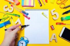 L'étudiant fait des notes dans un carnet Copiez l'espace Instruisez les accessoires sur un bureau sur un fond jaune Concept d'édu photos libres de droits