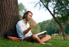 L'étudiant gai avec des écouteurs en parc de campus a lu un livre Image stock