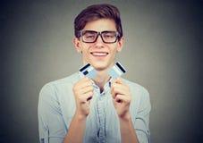 L'étudiant libre de dette heureuse tenant une carte de crédit a coupé dans deux morceaux Photos stock