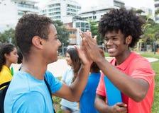 L'étudiant masculin africain donnent la haute cinq à l'étudiant indien Photographie stock libre de droits