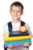 L'étudiant mignon est les livres et la pomme de fixation. d'isolement Photos stock