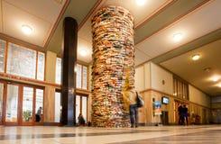 L'étudiant observant les livres irréels dominent dans la bibliothèque Photographie stock libre de droits