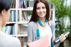 L'étudiant préparant une licence offre un livre à son ami Photo stock