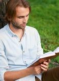 L'étudiant sérieux en parc de campus a lu un livre Photo libre de droits