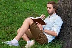 L'étudiant sérieux en parc de campus a lu un livre Image stock