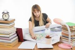 L'étudiante étudiant le programme-cadre de dessin d'étude à la table a encombré avec des livres photo libre de droits
