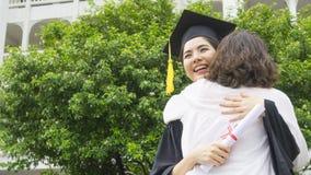 L'étudiante avec les robes d'obtention du diplôme et le chapeau étreignent le parent dedans Image stock