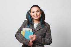 L'étudiante avec une pile de livres dans des ses mains regarde la caméra et les sourires plan rapproché photo stock