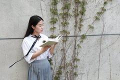 L'étudiante chinoise de lycée de l'Asie de belle beauté que le sourire apprécient le temps gratuit a lu un livre image stock