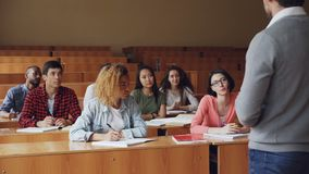 L'étudiante diligente de jolie jeune femme parle au haut maître d'école s'asseyant au bureau tandis que d'autres étudiants sourie banque de vidéos