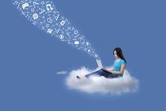 L'étudiante envoient l'email avec l'ordinateur portable sur le nuage Image stock