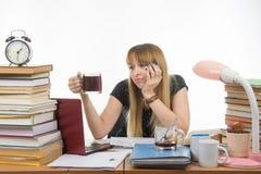 L'étudiante faisant la nuit regarde tristement une autre tasse de café Images libres de droits
