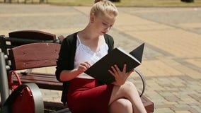 L'étudiante mignonne regarde des notes d'écriture en parc se reposant sur un banc banque de vidéos