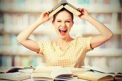 L'étudiante sauvage avec des verres crie avec des livres Photos stock