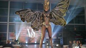 L'événement élégant, modèle dans le masque chic et dans le costume or-noir avec des ailes marche le long sur la piste clips vidéos