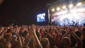 L'événement de roche, jeunesse de foule applaudissent sur le ?concert de musique en direct contre l'étape allumée lumineuse avec  clips vidéos