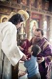 L'évêque orthodoxe donne la communion à un petit garçon Photos libres de droits