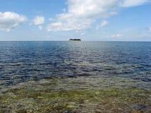 L'île isolée a détruit au milieu de la mer bleue images stock