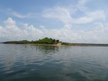 L'île verte et une route avec l'eau et le ciel Photos stock